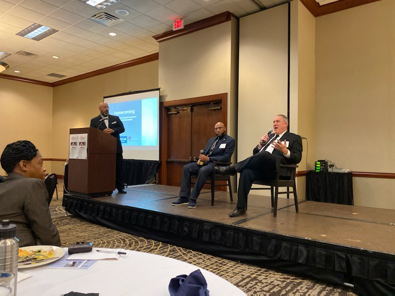 Joshua Hoe on the stage at a housing summit in Lansing Michigan discussing housing for formerly incarcerated people with Hakim Crampton and Troy Reinstra